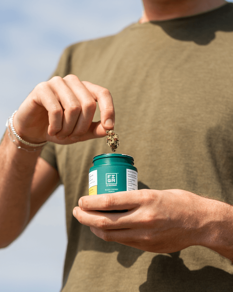 Man holding a cannabis bud outside of a green container