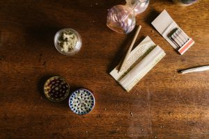 A weed grinder, dried cannabis flowers, rolling papers, and a pipe
